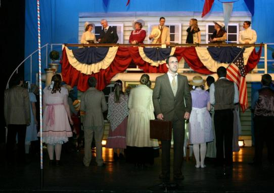 Cast member Benedict Hurley with ensemble on stage