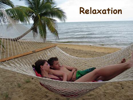 A woman and her son nap in a hamnock facing the Caribbean Sea. We offer all inclusive vacation packages in Belize.