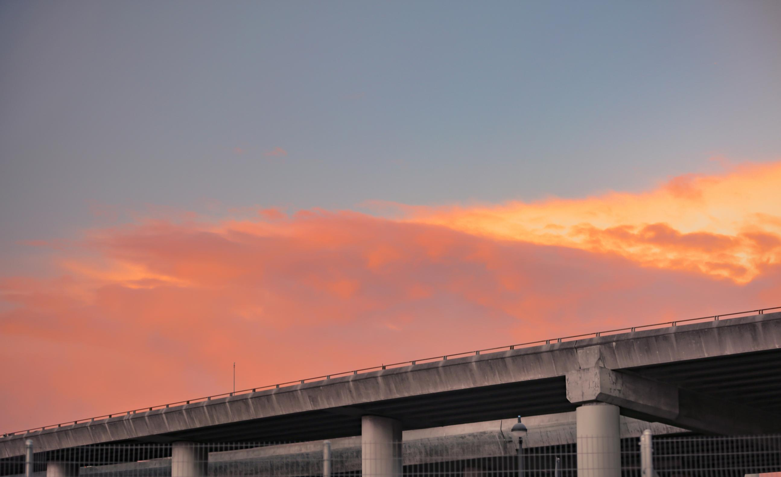 colorful clouds in sky with freeway city landscape