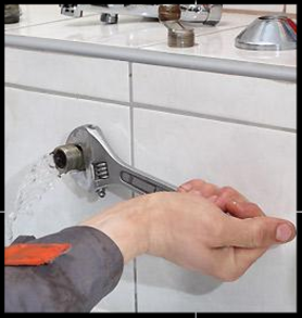 Using a wrench to turn off water supply.