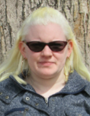 Outdoor picture of Susie, wearing sunglasses and looking at the camera