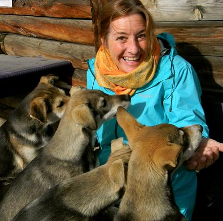 Beyond Skagway Tours guide plays with Alaskan Husky puppies on the Pet the Pups private Tour out of Skagway Alaska.