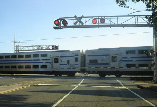 LIRR C3 Bi-level coaches at a grade level crossing in Bethpage, NY.