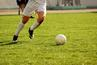 male soccer players legs on green field kicking soccer ball