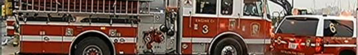 horizontal fire engine with ladder stowed, and fire chief's RV, visible from bottom of chassis almost to top of fire engine, on grey daytime street in emergency