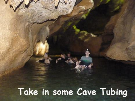 A family floats on inner tubes through an underground river in one of Belize's famous caves. Belize Adventure Tours