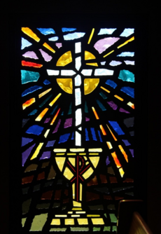 "Stained glass window representing ""Sacrament of the Altar (Holy Communion)"". This window features a white cross above a golden yellow chalice. The front of the chalice features on of the earliest forms of christogram, the superimposition of the Greek letters chi and rho. Behind the white cross is a yellow sun with rays radiating from the core to the edges of the window."