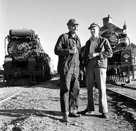 Texas and Pacific Railway Company Engineer Homer Parrish standing with another engineer in front of locomotives 644 and 706 at Marshall, Texas in 1946.