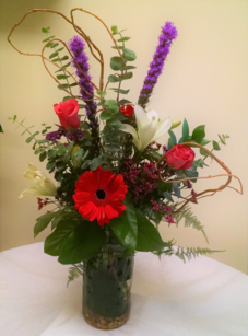 Vase arrangement designed with gerbera daisies, roses, lilies, curly willow, and a variety of foliage