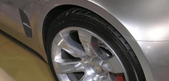 Close in shot of luxury sports car alloy wheel fender and low profile tire