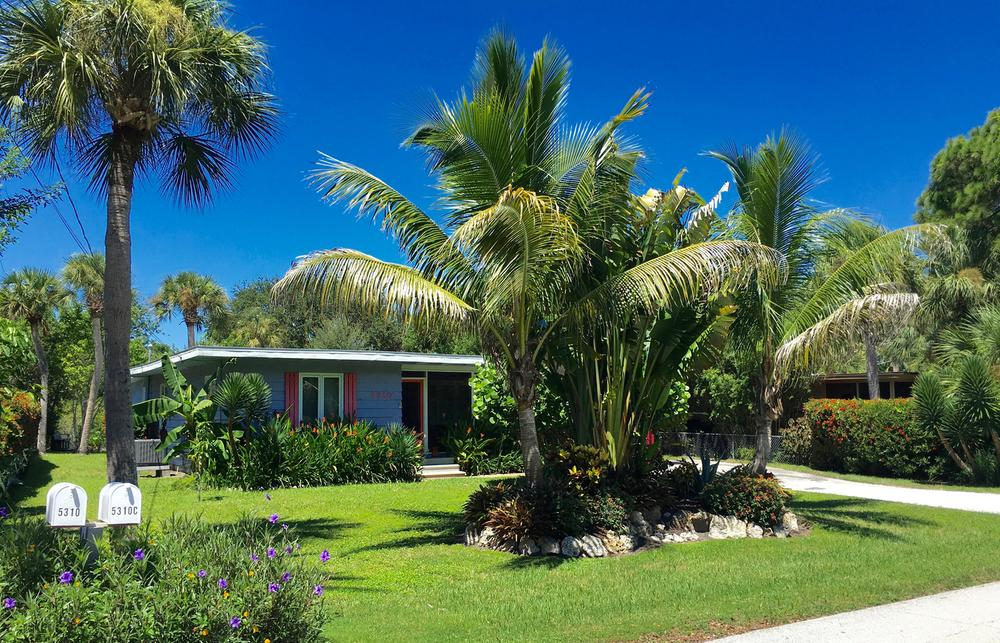Blue Lagoon Siesta Bungalow with lush yard and palm trees.