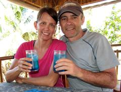 A couple toasts to their Belize Vacation with a Caribbean blue cocktail of curacao, rum and pineapple juice. All Inclusive Vacation Packages