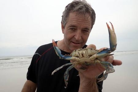 Man holding a live blue crab on beach