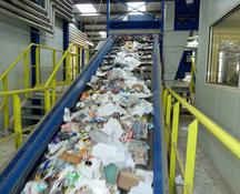 Paper to be shredded travels up the conveyor belt
