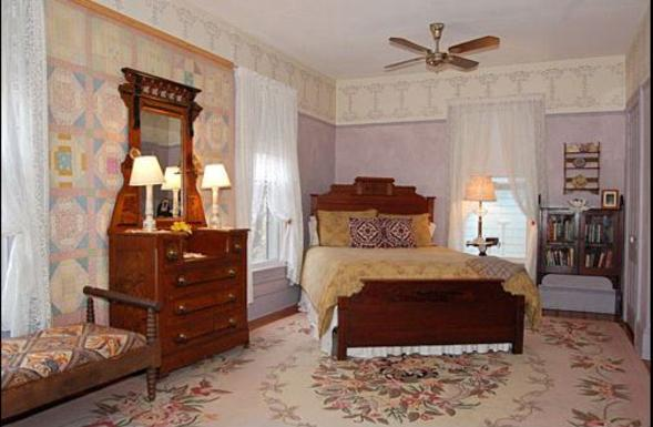 Wedgwood Accommodations - Image of the Lavendar Room with antique bed, dresser, bench, stenciled walls, lace curtains