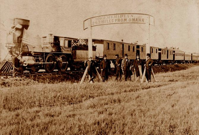 Directors of the Union Pacific Railroad gather on the 100th meridian, which later became Cozad, Nebraska, approximately 250 miles (400 km) west of Omaha, Nebraska Territory, in October 1866. The train in the background awaits the party of Eastern capitalists, newspapermen, and other prominent figures invited by the railroad executives.