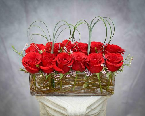 A dozen of astonishing red roses with pink wax and bear grass designed in a beautiful, long glass vase.