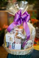 Custom gourmet basket filled with sweets and wrapped with a colorful ribbon.