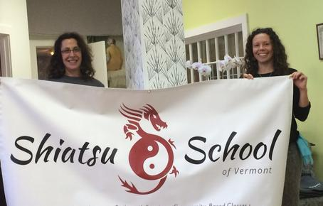 two instructors at the Shiatsu School of Vermont holding up a banner