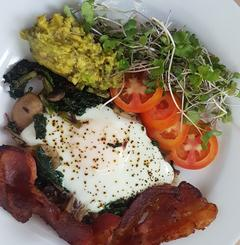 A healthy breakfast of bacon, eggs, saute mushrooms and spinach next to slices tomatoes, avocado and sprouts. Belize Vacation Packages