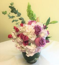 Hydrangea, Bells of Ireland, Roses, and Lilies.
