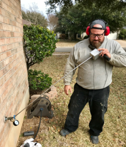 Photo of the master plumber wearing earphones and using a special tool that looks like a metal stick to listen for leaks in a hosebib outside a house