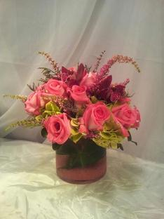 Vase arrangement designed with pink roses, dendrobium orchids, green hydrangea, and a variety of foliages.