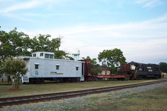 A short train of all Georgia Central Railway equipment comprised of U23B GC 3933, bulkhead flatcar GC 6020, and caboose GC 100 in downtown Vidalia, GA.