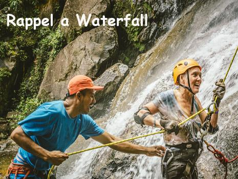 A local guide assists a woman who has just completed a rappel down a waterfall in Belize. Belize Adventure Tours
