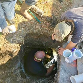 Photo of a plumber outside leaning into a trench with a long pipe in it, showing sewer line repair