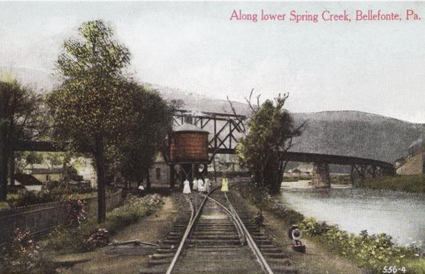 Postcard view of the Central Railroad of Pennsylvania viaduct in Bellefonte, Pennsylvania. The view looks north along the Pennsylvania Railroad Bellefonte Branch tracks passing under the viaduct, with Spring Creek to the right. Viaduct depicted existed between 1899 and 1919.