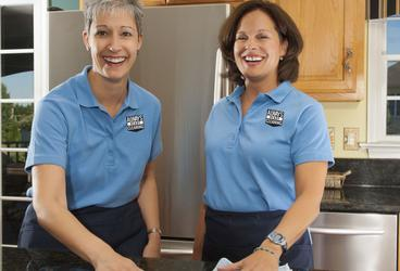 Professional house cleaners. Picture of two Always Ready Cleaning employees cleaning a kitchen.