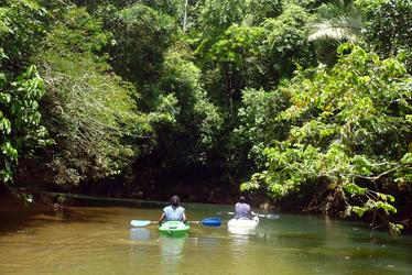 Two people kayaking down the Manatee river in Belize. Belize Adventure Tours