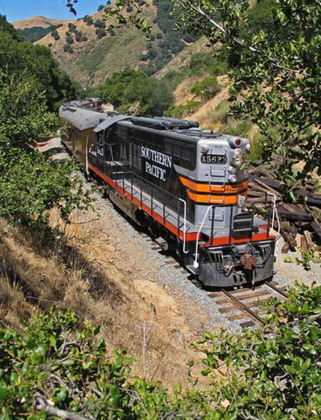 A passenger train pulled by Southern Pacific GP-9 No. 5623 travels east from Niles toward Sunol on the Niles Canyon Railway.