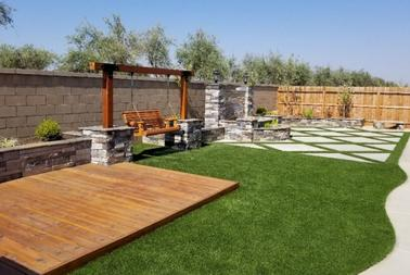 California Turf & Landscaping: Landscapers and landscaping design company - picture of backyard with deck, swing, and synthetic grass landscape