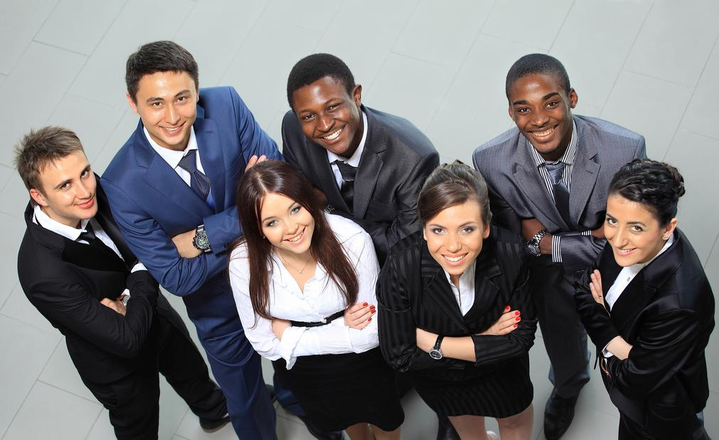 Workforce Development. Image of young people dressed professionally looking up smiling.