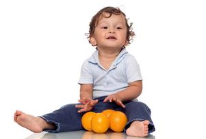 Toddlers playing with oranges