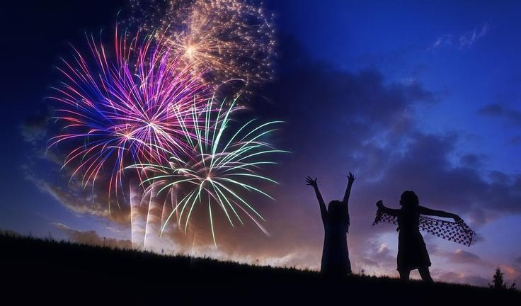 fireworks at evening, with two girls silhouetted celebrating on a hill