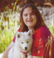 Outdoor picture of Ashley holding her dog, smiling, looking at the camera.