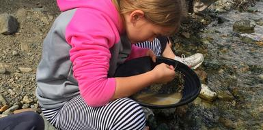 using salted pans, girl pans for gold in the Yukon, learning the placing gold panning technique used by prospectors during the Klondike Gold Rush