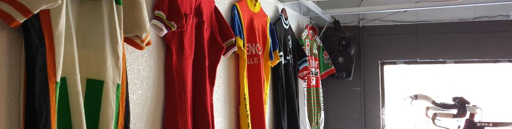 Vintage cycling jerseys hanging on the wall at Boulder Bicycle Works