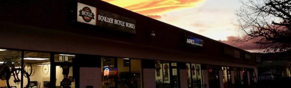 Boulder Bicycle Works Bike Shop store front under a glowing orange sky