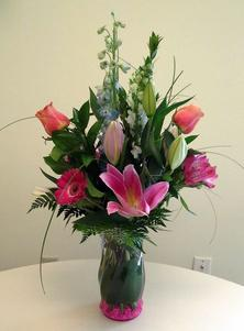 Vase arrangement designed with pink lilies, roses, gerbera, delphinium, pink gravel, and a variety of foliages.