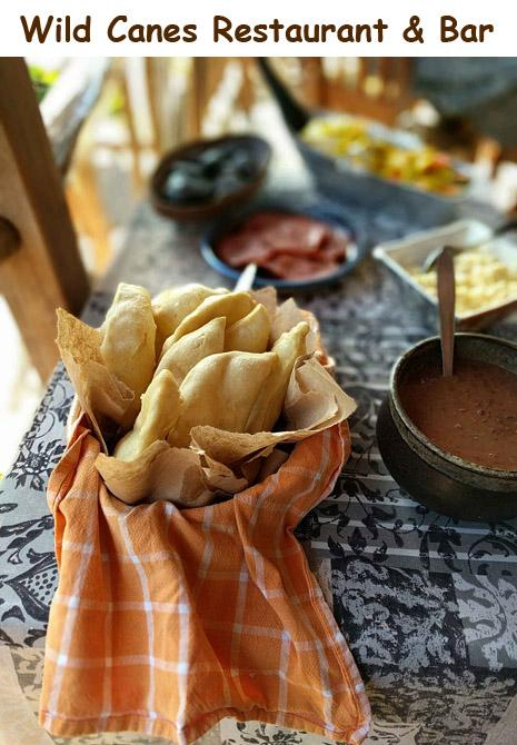 A basket of Belizean fry jacks and refried beans sit on a buffet table ready for breakfast. All Inclusive Vacations!