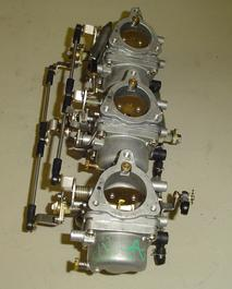 Set of used carburetors for a ​1987 or 1988 75 hp Suzuki outboard motor.