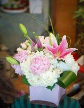 Designed in a pink glass cube, Beautiful combination of white hydrangeas and pink oriental lilies.