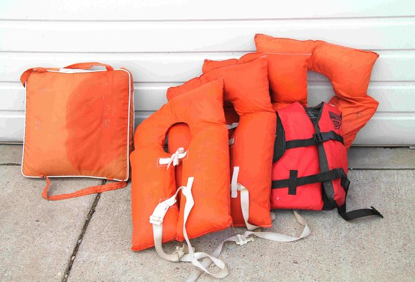 Assortment of Life Jackets and Cushions