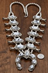Sterling squash blossom with nineteen White Buffalo stones by Augustine Largo, Navajo