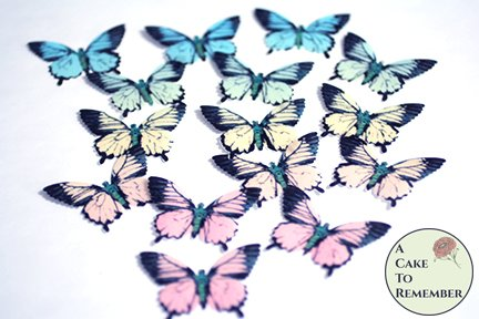 "15 pastel rainbow wafer paper cake topper edible butterflies. 2"" wide."