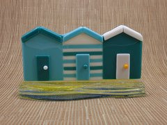 Beach huts in turquoise and blue glass in a sandy yellow and blue wave glass stand